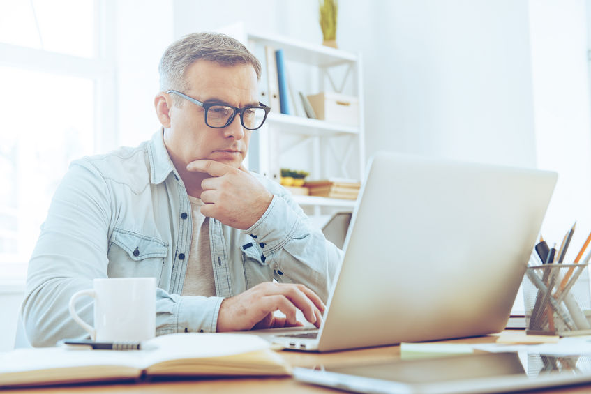 man looking thoughtfully at laptop